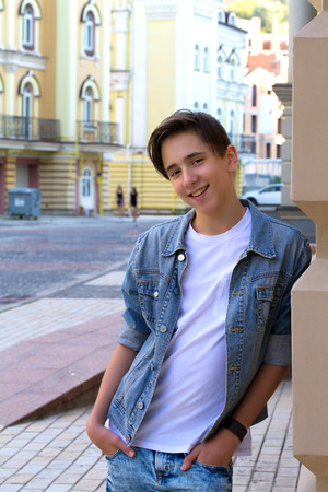 Portrait of handsome attractive teen boy smiling and staying outdoors close to the old wall