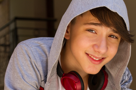 Outside portrait of teen boy. Handsome teenager  smiling and sitting on the stairs alone