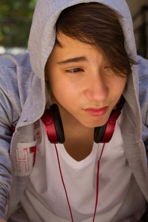 adolescente: Retrato exterior de la melancolía y triste muchacho adolescente sentado en las escaleras por sí solas