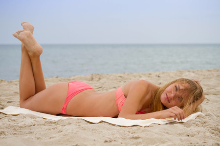 adolescent sexy: Young beautiful girl in bikini sunbathing on the beach; freedom summertime concept