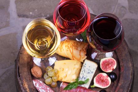 pan y vino: Rojo, rosa y blanco vasos y botellas de vino. Queso, higo, uva, jamón y pan en barril de madera viejo. Vista desde arriba, foto de estudio superior