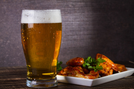 Glass of beer and chicken wings on dark wooden background