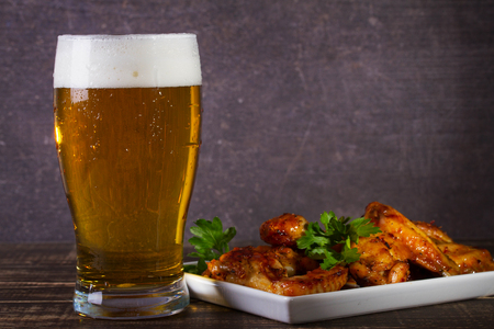 real ale: Glass of beer and chicken wings on dark wooden background