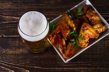 Glass of beer and chicken wings on dark wooden background. View from above, top studio shot