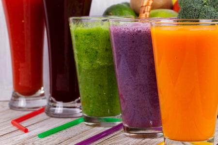 Healthy Colorful Smoothies with Fruits and Vegetables Against a Rustic Wooden Background. Various Freshly Squeezed Juices for Detox 免版税图像