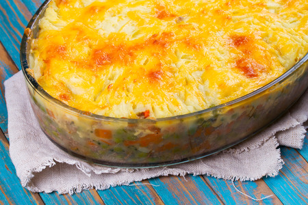 shephard: Potato, cheese, meat, carrot, onion and green peas casserole on blue wooden background