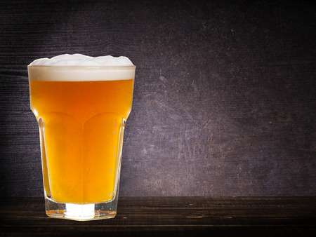 real ale: Glass of beer against dark wooden background, with copyspace