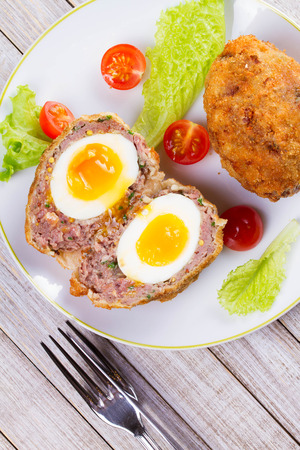 cooked pepper ball: Scotch Eggs Served with Tomato Cherry and Salad on White Plate. View From Above, Top Studio Shot