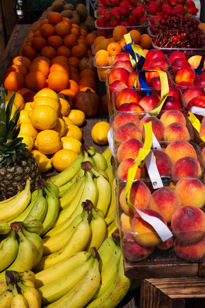 Apples, lemons, oranges, pomegranates, pineapples, peaches and strawberry. Various fruits in a street market