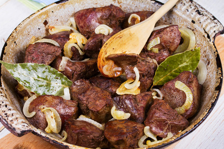 Sauteed liver with onions in pan.