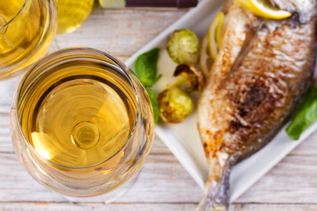 Glasses and bottle of white wine. Grilled dorado fish with vegetables in white plate. View from above, top studio shot