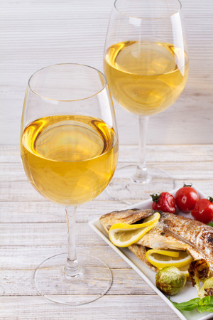 Glasses and bottle of white wine. Grilled dorado fish with vegetables in white plate
