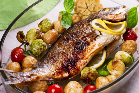 Roasted dorado fish with brussels sprouts, tomatoes, garlic, young potato and greens