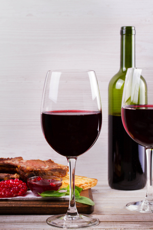 Red wine glasses and bottle. Rack of lamb with pomegranate sauce and greens Stock Photo
