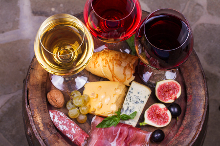 Red, rose and white glasses and bottles of wine. Cheese, fig, grape, prosciutto and bread on old wooden barrel. View from above, top studio shot of vegetables and fruits Stock Photo