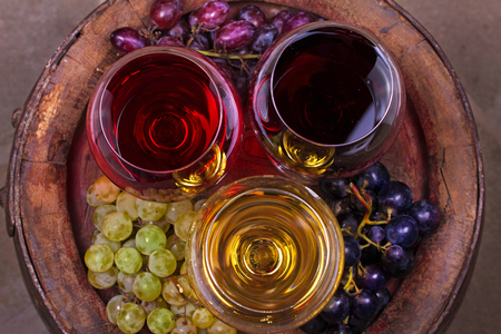 Red, rose and white glasses of wine. Grape, fig, nuts and leaves on old wooden barrel. View from above, top studio shot of vegetables and fruits Stock Photo