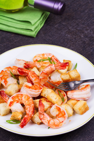 Shrimp with crispy croutons and scallions in white plate. White wine bottle