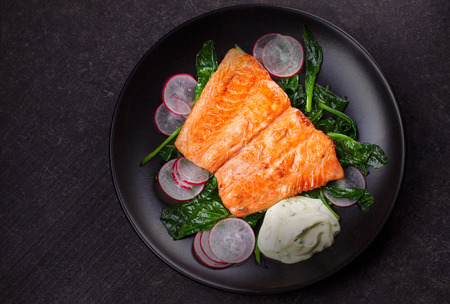 broiled: Broiled salmon with radish and spinach, served on black plate. View from above, top studio shot