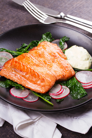 broiled: Broiled salmon with radish and spinach, served on black plate Stock Photo