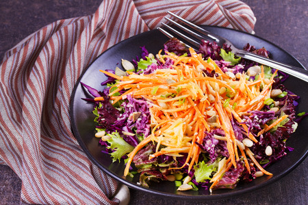 Red and white cabbage, carrot, lettuce, spring onion, nuts and seeds salad. Winter salad