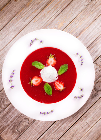 Strawberry soup with ice cream and mint. Pureed strawberries garnished with mint leaves topped with vanilla ice cream. Blended berries. Berry dessert. View from above, top studio shot