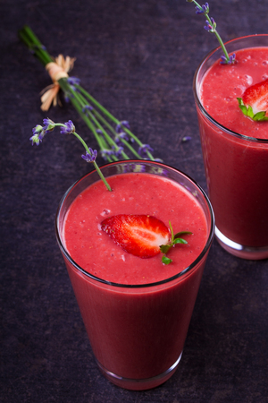 Berry smoothie garnished with strawberries and lavender flowers on dark wooden background