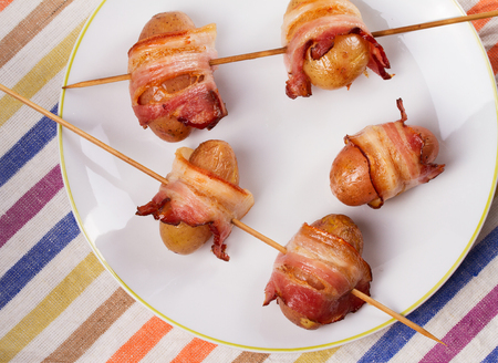 Bacon wrapped potato on  skewers on white plate. View from above, top studio shot