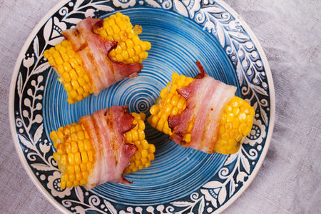 Bacon wrapped corn on blue plate. View from above, top studio shot