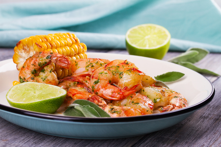 Grilled shrimps and corn garnished with lime and sage leaves. Prawns on white plate Stock Photo