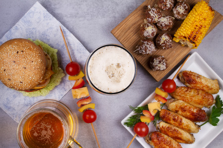 real ale: Glasses of beer with chicken wings, burger, meat balls, grilled corn and vegetables. Beer bites. Ale and food still life. View from above, top studio shot