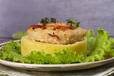 Fish patty with mashed potato and lettuce