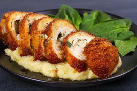 Chicken Kiev on mashed potato with spinach. Breaded chicken breast stuffed with herbs and butter on black plate 版權商用圖片