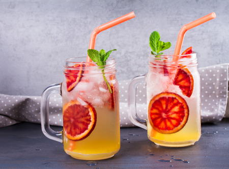 Bloody orange cocktail garnished with mint in the jars