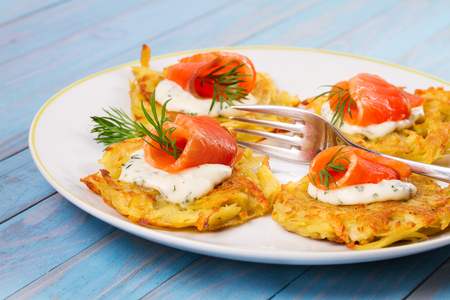 brown trout: Potato Pancakes With Salmon. Vegetable fritters with fish. Latkes on a plate Stock Photo