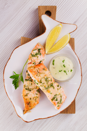 Baked salmon with parmesan and herbs, lemon and sauce. Fish with cheese on white plate. View from above, top studio shot