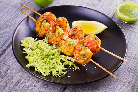 Cilantro grilled shrimps on skewers with sesame napa cabbage, green butter sauce and lemon. Skewered prawns on black plate
