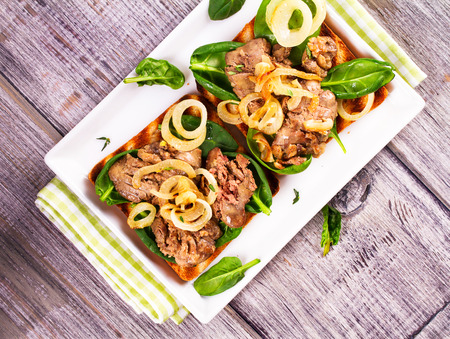 sauteed: Chicken Liver, Spinach and Onion Sandwiches on White Plate. View from above, top studio shot Stock Photo