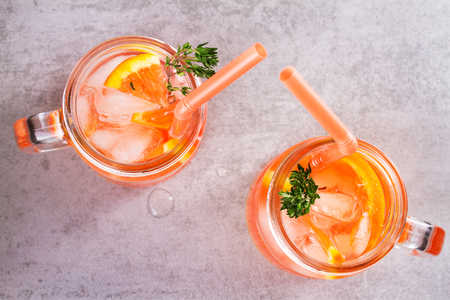 Campari and vermouth cocktail with oranges, garnished with thyme. View from above, top studio shot