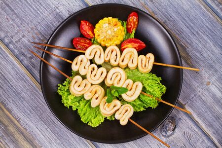 Grilled squid rings on skewers and vegetables on black plate. View from above, top studio shot