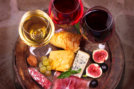 Glasses of red, rose and white wine with grape, figs and walnuts in wine cellar. Food and drinks concept. View from above, top studio shot