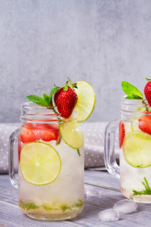 Strawberry mojito. Detox fruit and berry infused flavored water in jars. Refreshing summer homemade cocktail Stock Photo