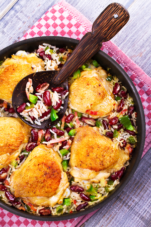 halved  half: Chicken with Rice, Beans, Bacon and Green Pepper in Pan. View from above, top studio shot Stock Photo