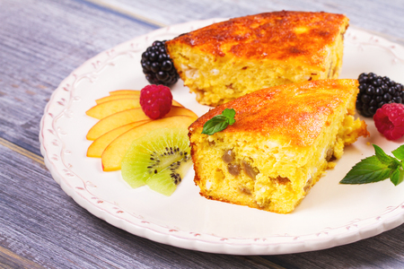 Cheesecake, garnished with berries and peach