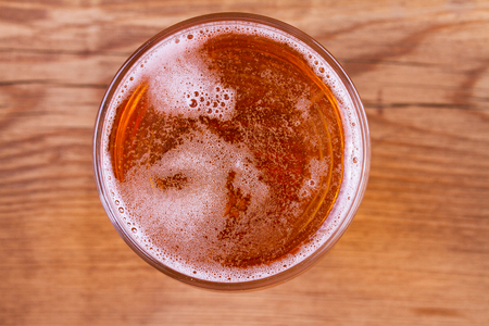 Glass of beer on wooden background. View from above, top studio shot