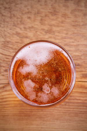 real ale: Glass of beer on wooden background. View from above, top studio shot
