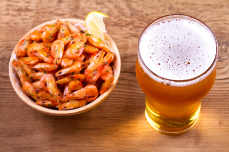Glass of beer and shrimps on wooden background. View from above, top studio shot