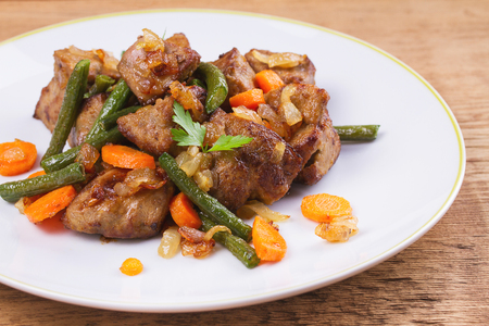 Sauteed liver with vegetables on white plate