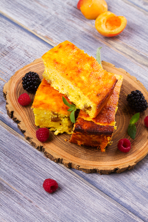 Cheesecake, garnished with berries, mint and peach. Sweet farmer cheese (cottage cheese) casserole