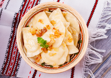 fillings: Varenyky, vareniki, pierogi, pyrohy or dumplings, filled with potato and served with salty caramelized onion. View from above, top studio shot, overhead Stock Photo