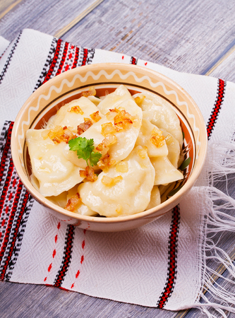 Varenyky, vareniki, pierogi, pyrohy or dumplings, filled with potato and served with salty caramelized onion Stock Photo